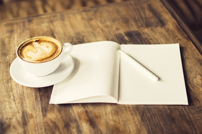 Cup of coffee and blank diary with a pencil on a wooden table
